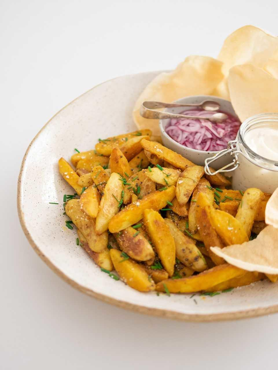 Bombay potatoes with a roasted garlic aioli, popadoms and pickled red onions